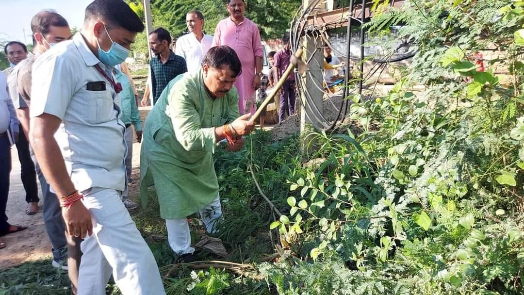 कुल्हाड़ी से झाड़ियों की सफाई करते ऊर्जा मंत्री प्रद्युमन सिंह तोमर। - Dainik Bhaskar