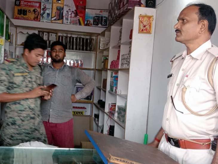 मोबाइल दुकान में छानबीन करती पुलिस। - Dainik Bhaskar