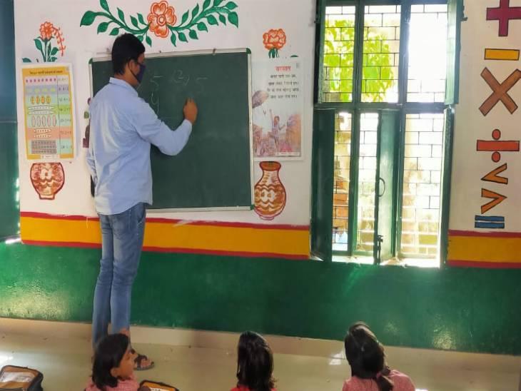 वाराणसी के एक सरकारी स्कूल में बच्चों को पढ़ाते शिक्षक।