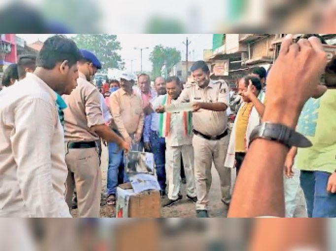 पानी डालकर पुतले की आग को बुझाते पुलिस कर्मी। - Dainik Bhaskar