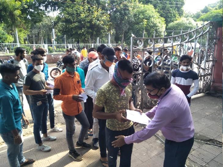 परीक्षा सेंटर के बाहर परीक्षार्थी की तलाशी लेते शिक्षक, साथ ही कोविड गाइडलाइन का पालन न करने वालों को प्रवेश नहीं दिया गया
