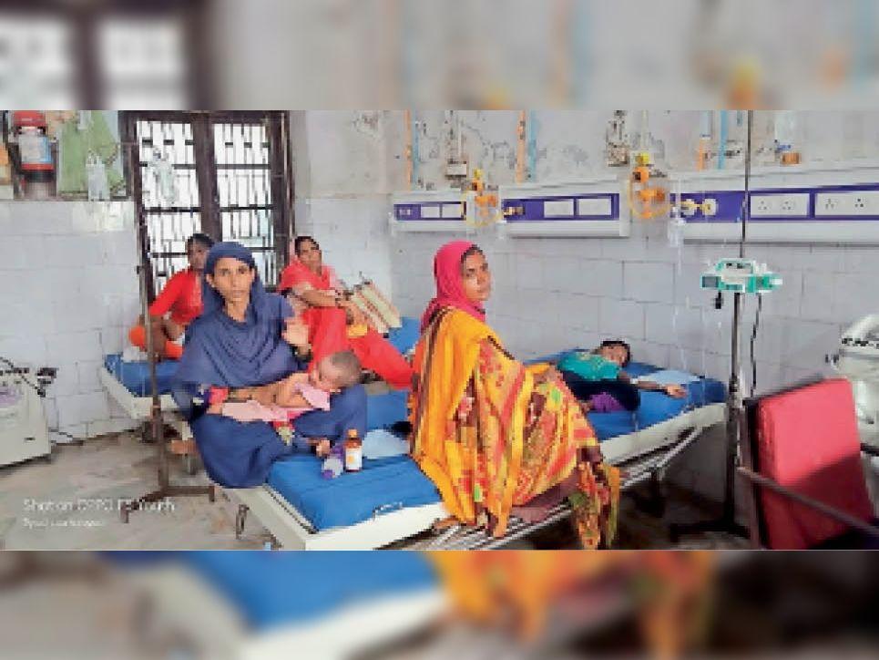 डीएमसीएच के शिशु विभाग के इमरजेंसी में एक ही बेड पर दो बच्चे इलाज करती महिला। - Dainik Bhaskar