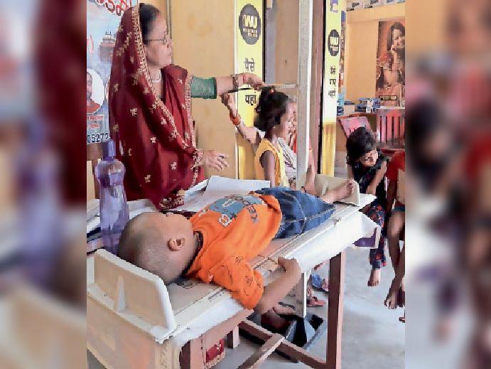 चैनपुर आंगनबाडी केंद्र में बच्चे का वजन लेती सेविका। - Dainik Bhaskar
