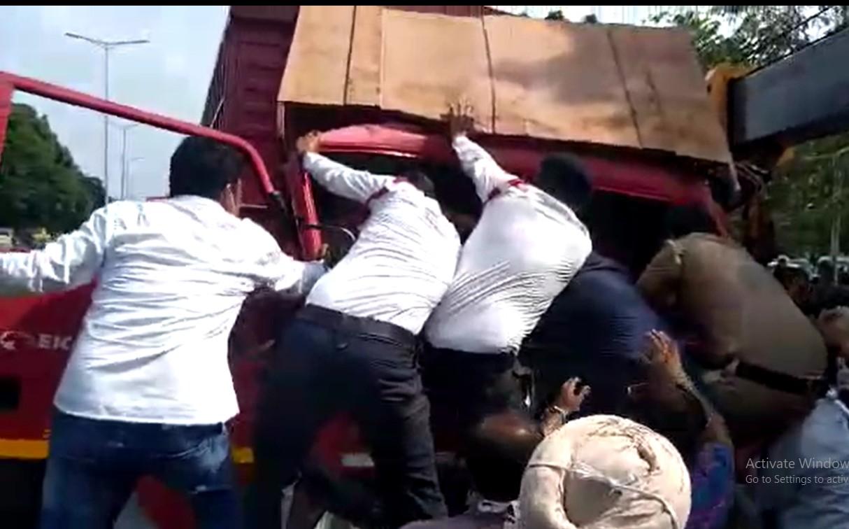 महिला कॉन्स्टेबल को ट्रक से बाहर निकालने की कोशिश करते पुलिसकर्मी।