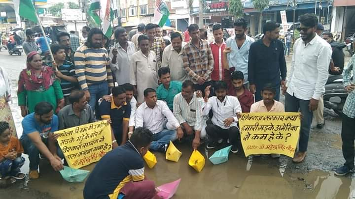 नरेला विधानसभा क्षेत्र में कांग्रेस कार्यकर्ताओं ने गड्ढों में चलाई नाव। - Dainik Bhaskar