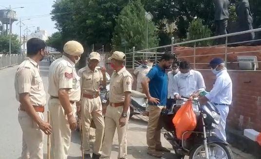 एमजी हॉस्पिटल के बाहर लोगों को रोकती पुलिस।