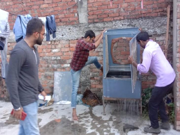 इस्माइलगंज में कूलर में जमा पानी निकालते स्वाथ्यकर्मी।