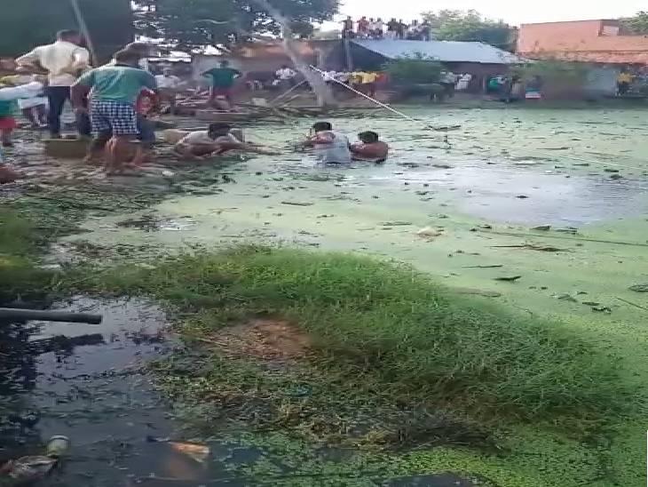 महिला को तालाब से निकालते गोताखोर। - Dainik Bhaskar