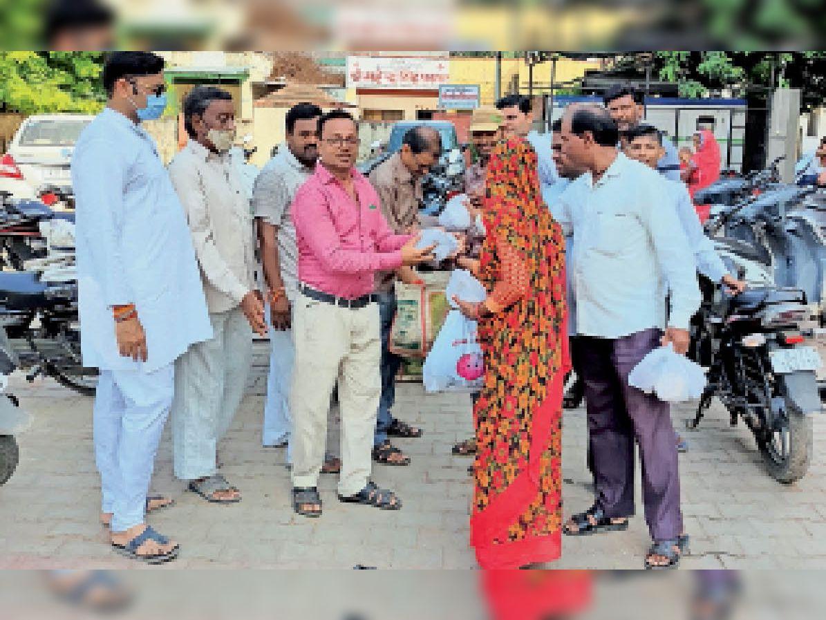 अस्पताल में मरीजाें के तीमारदाराें काे भाेजन के पैकेट बांटते सदस्य। - Dainik Bhaskar