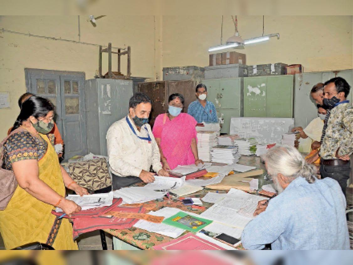 कन्या उच्चतर माध्यमिक विद्यालय सराफा में केंद्र प्रभारी को परीक्षार्थियों की उत्तर पुस्तिका जमा करते शिक्षक। - Dainik Bhaskar