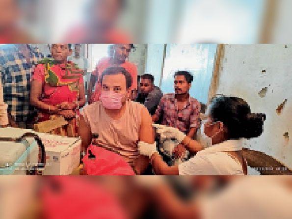 दिघलबैंक के धनतोला आयोजित कैम्प में टीका लगवाते युवक।