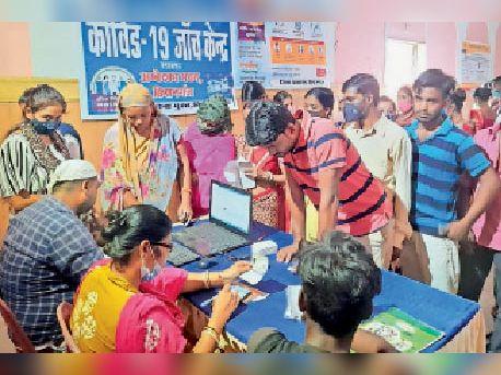 शहर के टाउन हॉल स्थित टीकाकरण केन्द्र में वैक्सीन लेने के लिए खड़े लोग। - Dainik Bhaskar