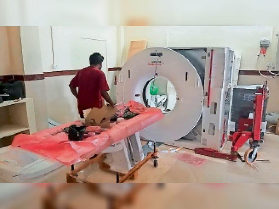 जिला अस्पताल के कक्ष में मरीजों की जांच के लिए सीटी स्कैन मशीन सेट करता कर्मचारी। - Dainik Bhaskar