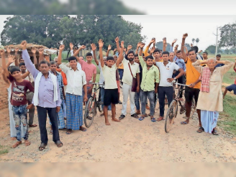 सड़क निर्माण की मांग को लेकर प्रदर्शन करते ग्रामीण। - Dainik Bhaskar