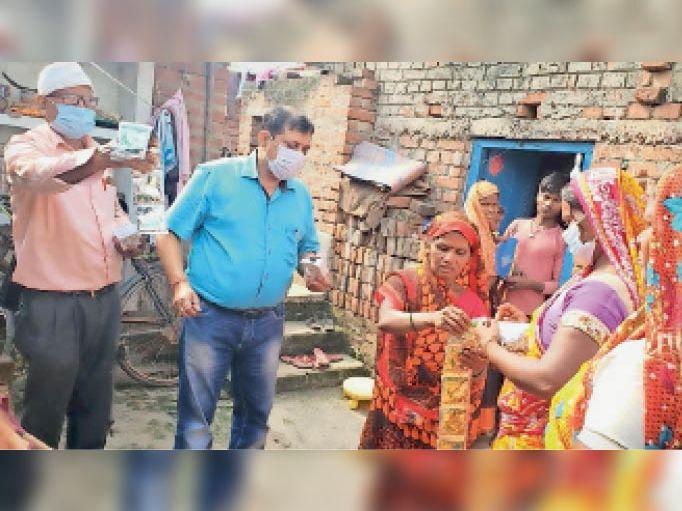 ग्रामीणों को ओआरएस घोल का पैकेट देते चिकित्सक। - Dainik Bhaskar