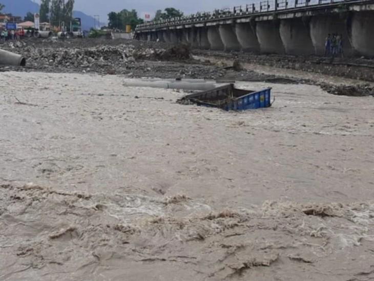 भारी बारिश के बाद जाखन नदी में बहा एक ट्रक। पुल नदी में बहने के बाद यहां लोग फंसे हुए हैं।