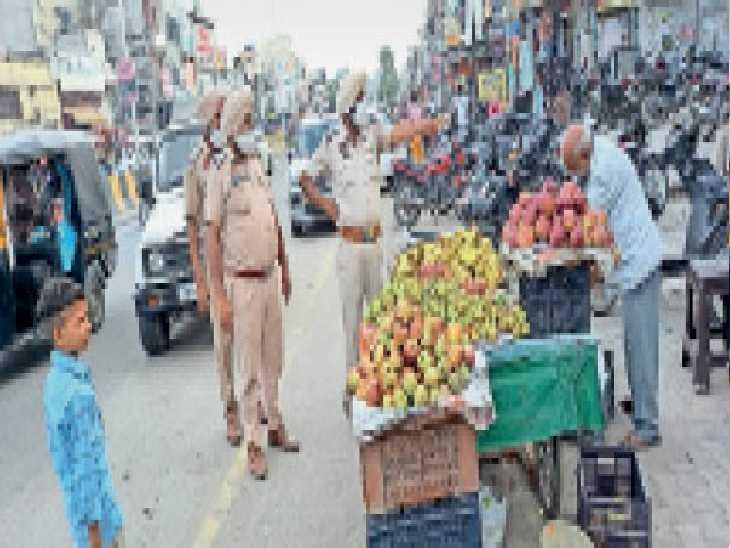 रोड पर लगी रेहड़ियों को हटवाते हुए पुलिस कर्मचारी। - Dainik Bhaskar