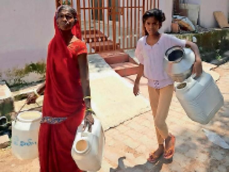 वार्ड 25 में पानी भरने जाती महिला और बच्ची। - Dainik Bhaskar