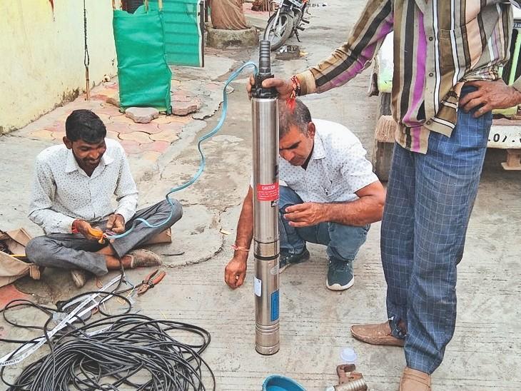नए बाेरिंग में माेटर उतारने की तैयारी करते कर्मचारी। - Dainik Bhaskar