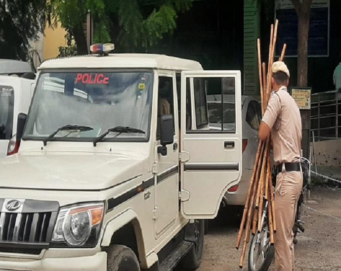 करनाल में साथियों की लाठियां गाड़ी में रखता पुलिस कर्मचारी।