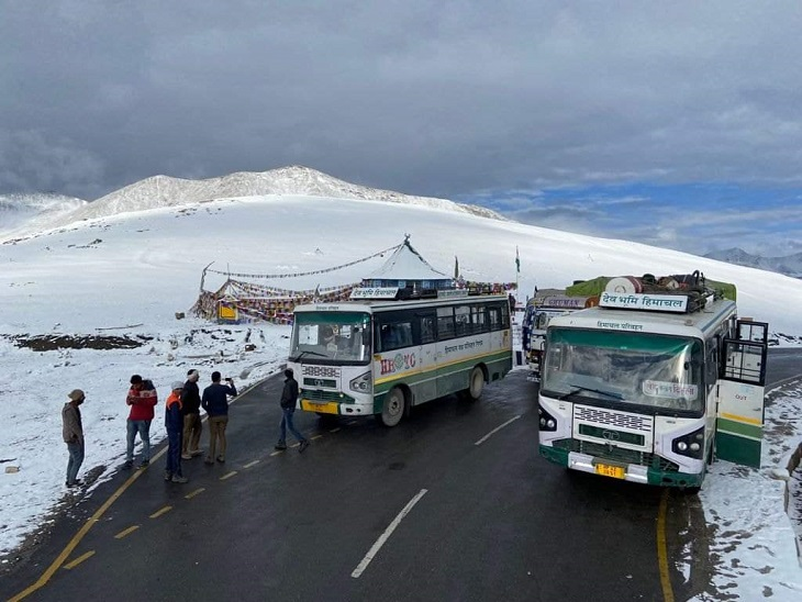 लेह-दिल्ली रूट पर जा रही बस को बीच में रोककर बर्फबारी का लुत्फ उठाते पर्यटक।
