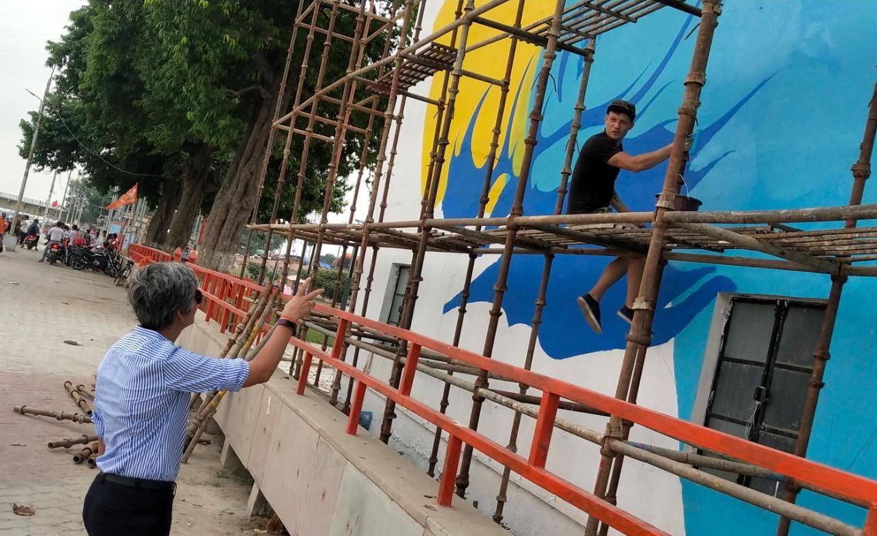 सरयूतट के पंप हाऊस की दीवार पर उकेरी जा रही श्रीराम के साकेतधाम गमन की तस्वीर