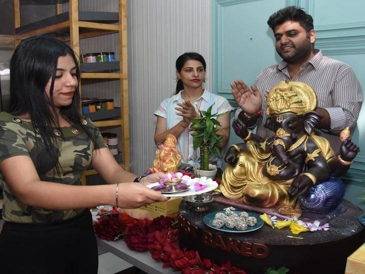 चॉकलेट से बने गणेश की पूजा करते लोग।
