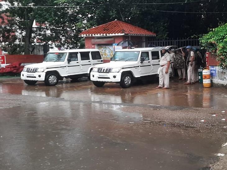 लघु सचिवायल के गेट पर बारिश से बचते हुए ड्यूटी पर तैनात पुलिसकर्मी।