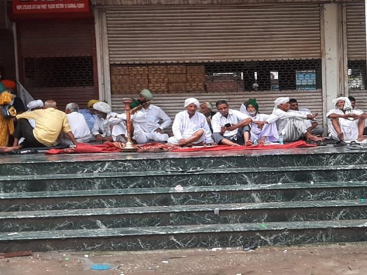 बारिश से बचने के लिए बरामदे में बैठे किसान। - Dainik Bhaskar