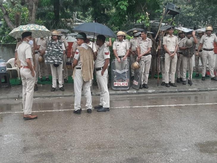 बारिश के बीच ड्यूटी पर डटे पुलिस कर्मी।
