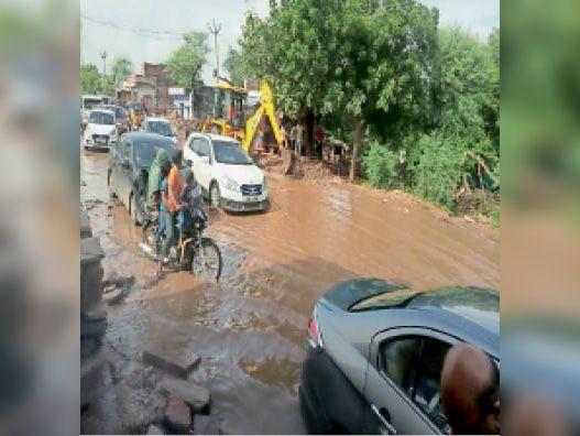 करसाई| महोली मोड़ के पास जमा पानी में निकलते वाहन, जेसीबी से नाली बनाई। - Dainik Bhaskar
