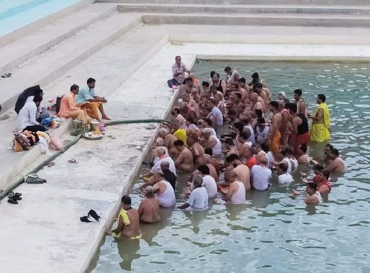 बीकानेर के धरणीधर तालाब में पानी आने के बाद श्रावणी कर्म करते लोग।