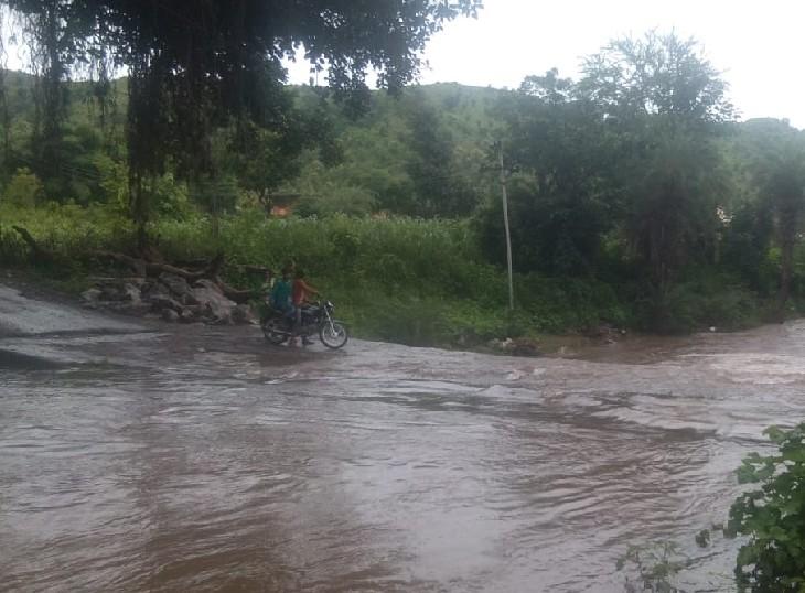 उदयपुर जिले में तेज बारिश के बाद बरसाती नाले में बहते पानी के बीच से गुजरते मोटर साइकिल सवार युवक।