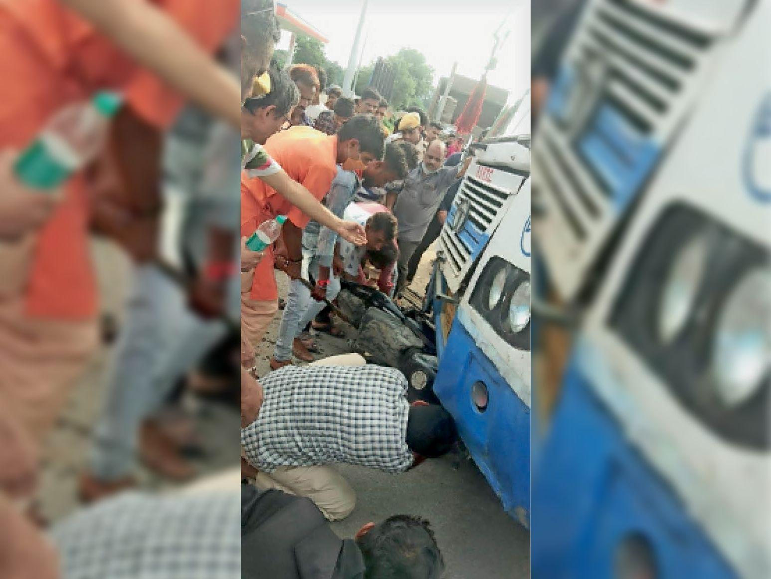 रोडवेज के नीचे फंसे लालशंकर और बाइक को निकालते ग्रामीण। - Dainik Bhaskar