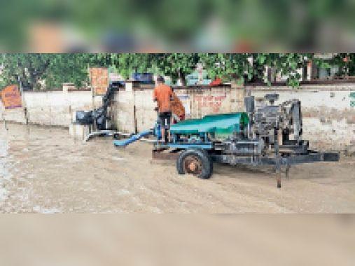 सुरखाब चौक पर पंप सेट लगाकर बरसाती पानी निकालते कर्मचारी। - Dainik Bhaskar
