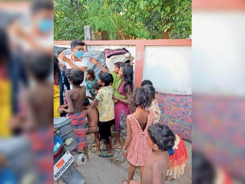 जरूरतमंद बच्चों में खाद्यान्न व बिस्कुट वितरित करता युवक। - Dainik Bhaskar