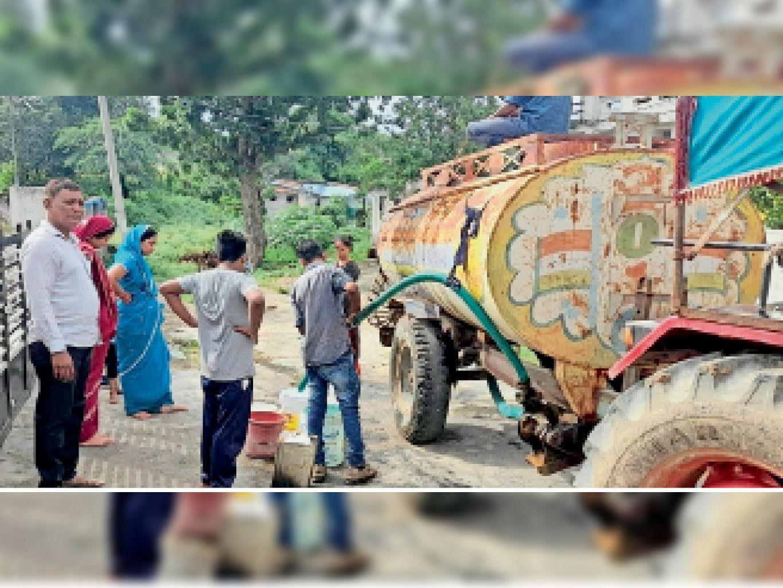 पुनर्वास कॉलोनी में पालिका द्वारा भेजे गए टैंकर से पानी भरते नागरिक। - Dainik Bhaskar