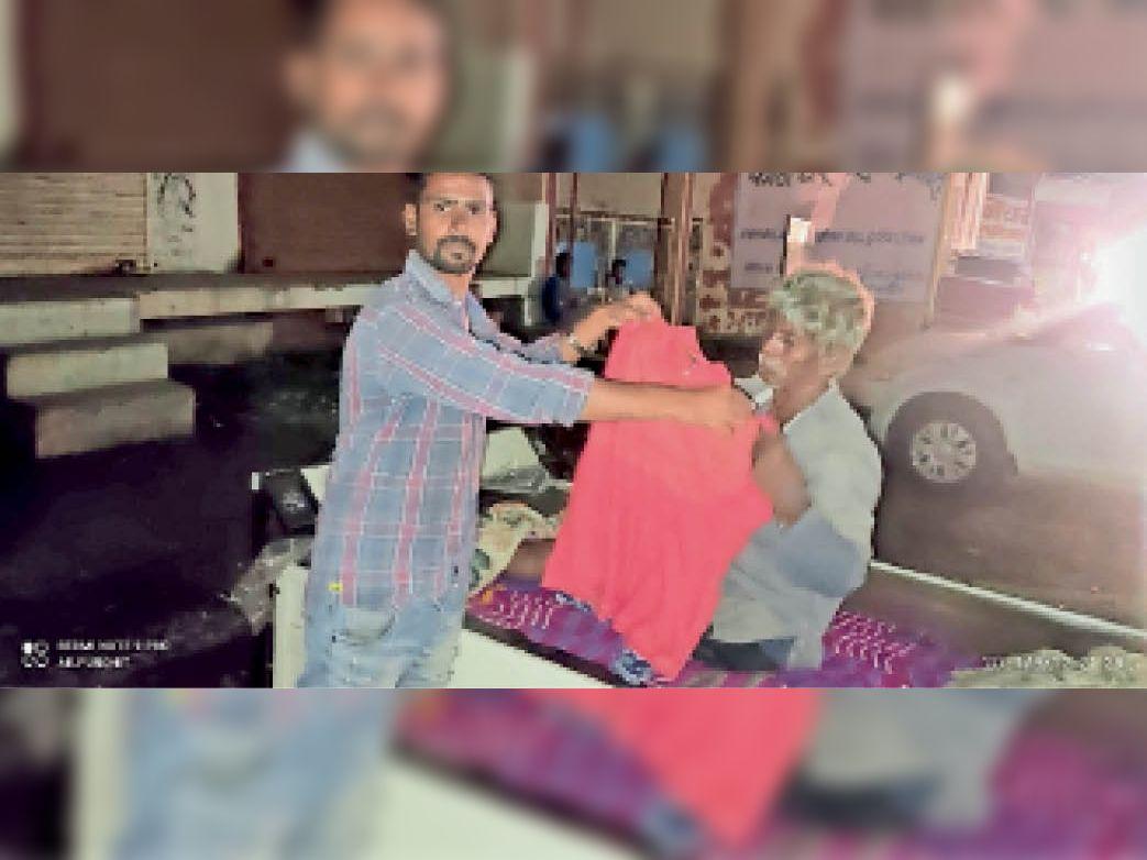 जरूरतमंदों को कपड़े का वितरण करते हुए परिवार के सदस्य। - Dainik Bhaskar
