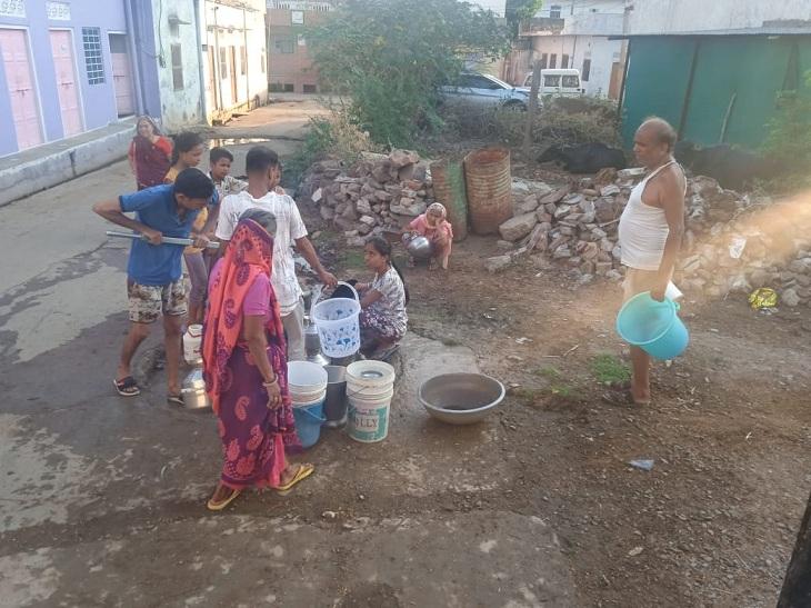 हैंडपंप से पानी भरते लोग। - Dainik Bhaskar