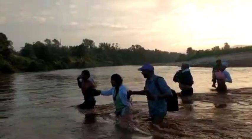 दुधी नदी को पार कर टीकाकरण दल डोलनी गांव पहुंचा।