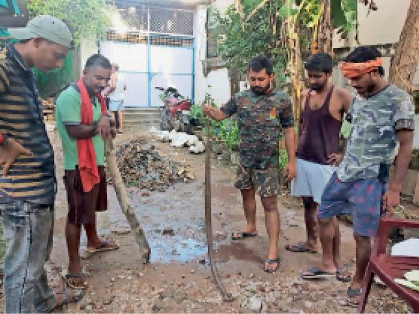 फ्रेंड्स कॉलोनी में मरे हुए सांप को दिखाते लोग। - Dainik Bhaskar