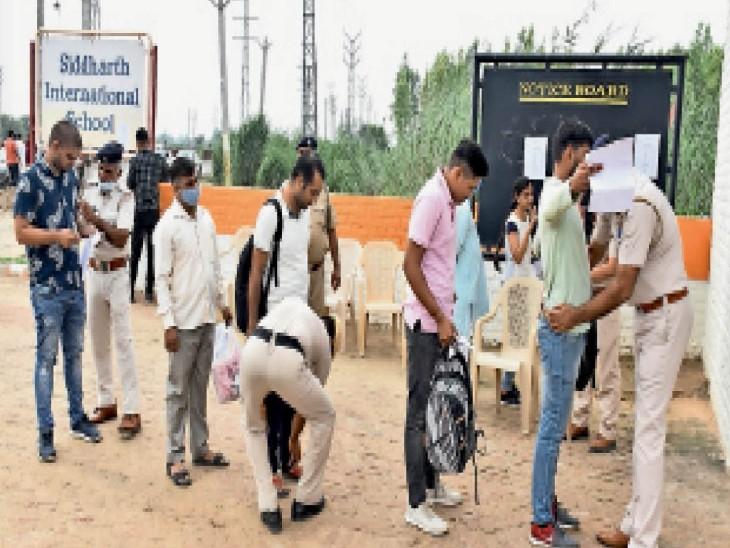 हिसार तोशाम रोड पर सिद्धार्थ इंटरनेशनल स्कूल में एचसीएस परीक्षा के लिए पहुंचे परीक्षार्थियों की चेकिंग करते हुए पुलिसकर्मी। हर परीक्षा केंद्र पर 11-11 पुलिस कर्मी तैनात किए गए। - Dainik Bhaskar