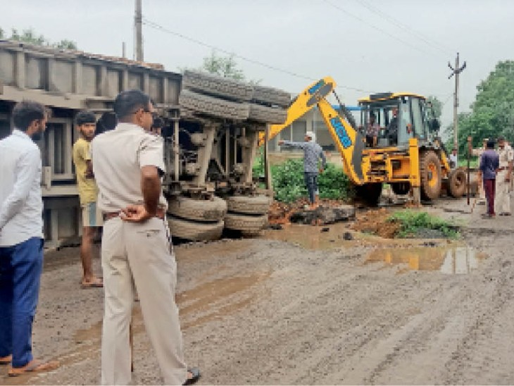 खैरथल मार्ग पर रोडियों से भरा पलटा हुआ ट्रोला व कुशालवास में क्षतिग्रस्त रोड। - Dainik Bhaskar