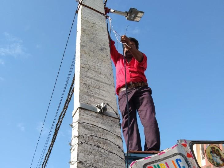 सूचना मिलने के बाद लाइन को काटते हुए बिजली कर्मचारी। - Dainik Bhaskar