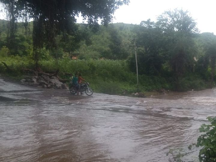 उदयपुर जिले में तेज बारिश के बाद बरसाती नाले से गुजरते बाइक सवार युवक।