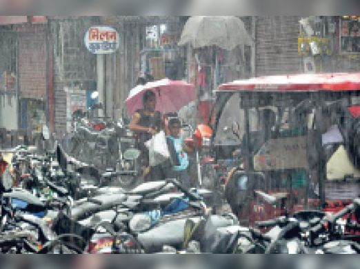 स्टेशन रोड में बारिश के दौरान छाता से बचाव करते लोग - Dainik Bhaskar