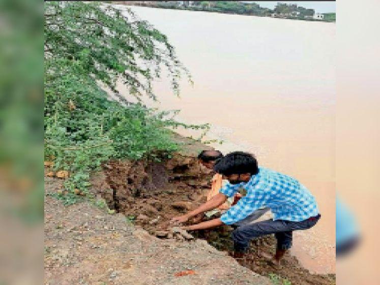 बालेर। तालाब की सुरक्षा दीवार टूटने के बाद मिट्टी के कट्टे लगाते हुए। - Dainik Bhaskar