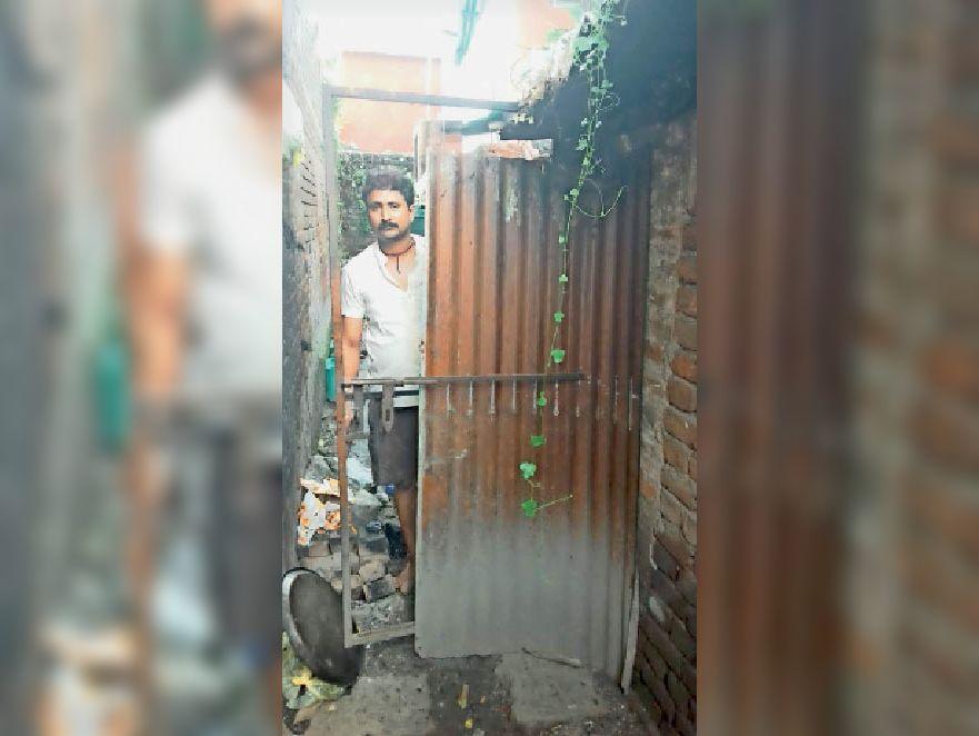 हरनौत में टूटे दरवाजे को दिखाता दुकानदार। - Dainik Bhaskar