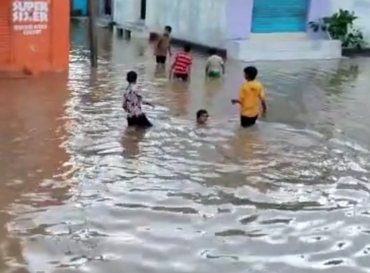 सड़क पर भरे पानी में नहाते बच्चे।