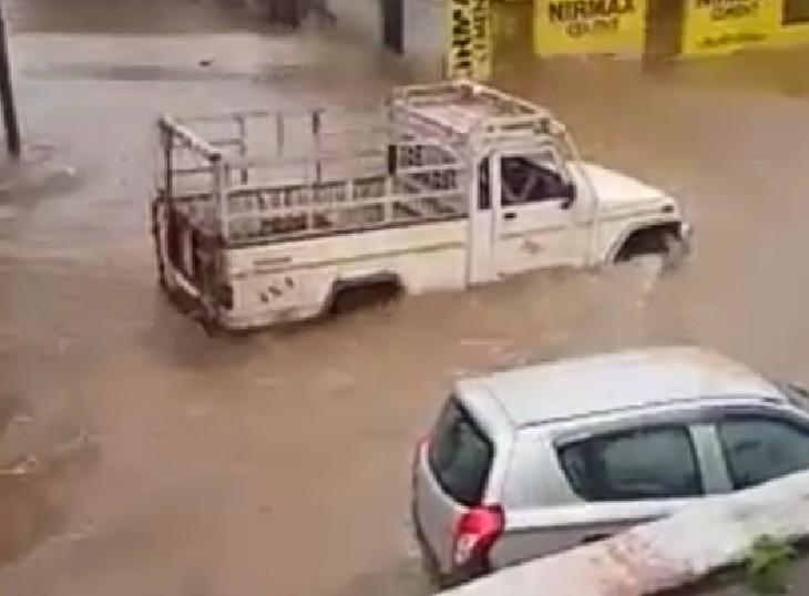 चूरू के रतन नगर में तेज बारिश के बाद भरे पानी से गुजरते वाहन।